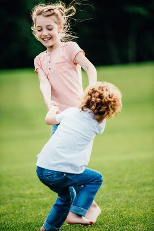 schattig broertje en zusje hand in hand en samen spelen in het park