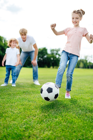 father with son looking at cute little girl kicking soccer ball on meadow Imagens - 102506565