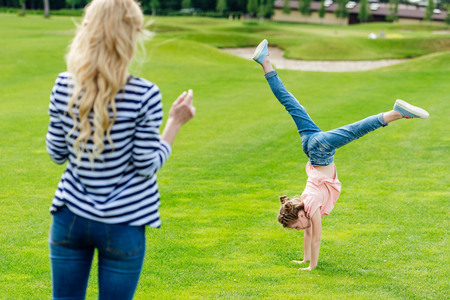 young mother looking at cute little daughter performing handstand on green grass in park