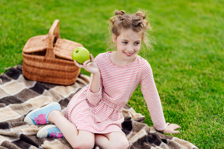 adorable smiling little girl holding green apple while sitting on plaid at picnic Banque d'images