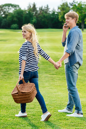 smiling young woman holding picnic basket and man talking on smartphone while walking together in park  Stock Photo