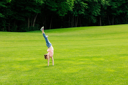 full length view of cute little girl performing handstand on green grass in park Stock Photo