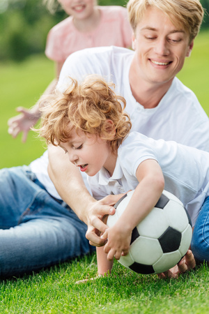 happy father and son playing with soccer ball on green grass at park  Stok Fotoğraf