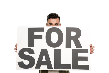 obscured view of man with for sale banner in hands looking at camera isolated on white