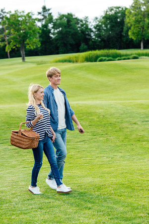 happy young couple with picnic basket and smartphone walking together on green lawn in park