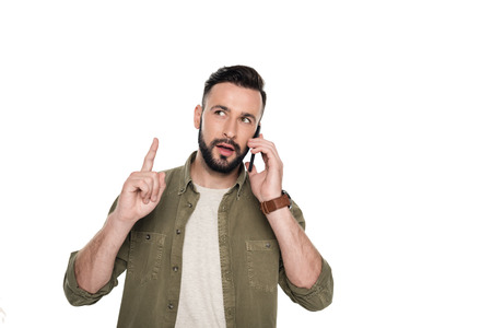 portrait of man pointing up while talking on smartphone isolated on white Stock Photo