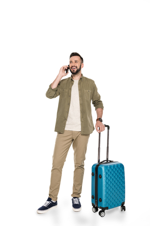smiling man with luggage near by talking on smartphone isolated on white