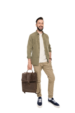 smiling bearded man holding bag and looking at camera isolated on white