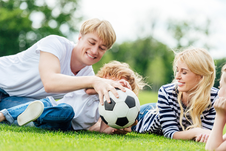 happy family with two kids having fun with soccer ball while lying on green meadow