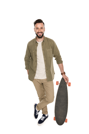 smiling man holding longboard and looking at camera isolated on white