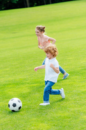 cute little brother and sister playing soccer on green grass in park Stock Photo