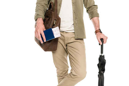 partial view of tourist with bag and umbrella holding passport and ticket in hand isolated on white Zdjęcie Seryjne