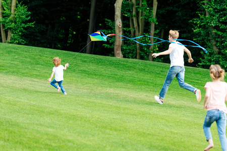 happy father with daughter and son playing with kite while running on green meadow in park Stock Photo