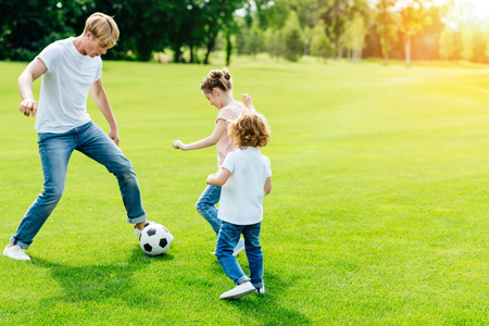 young father with cute little children playing soccer on green grass in park