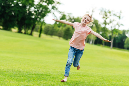 adorable happy little girl with open arms running on green grass in park Standard-Bild