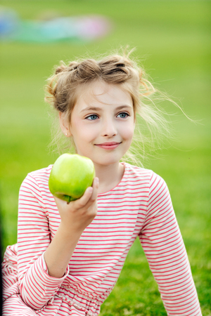 portrait of adorable smiling girl eating green apple while sitting on grass at park