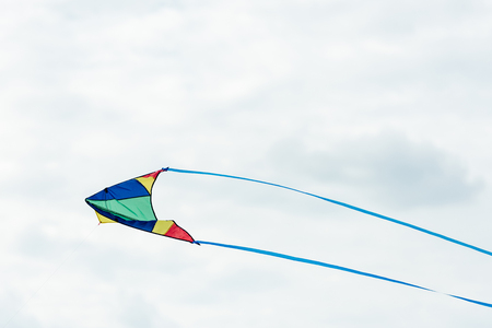 single colorful kite flying in cloudy sky at daytime Stock fotó