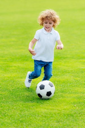 cute happy little boy playing soccer on green grass at park