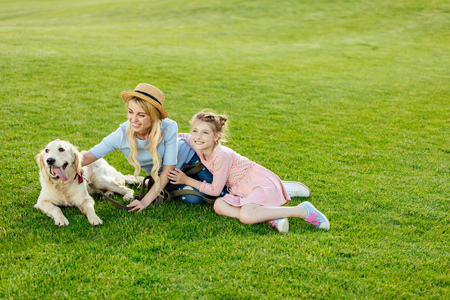 happy beautiful mother and daughter with golden retriever dog sitting on green lawn at park