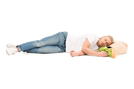 young caucasian man sleeping on paper bag with food isolated on white