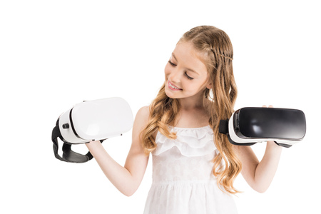 portrait of little girl holding virtual reality headsets in hands isolated on white Фото со стока