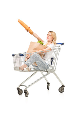 smiling woman pointing away with bread while sitting in shopping cart isolated on white