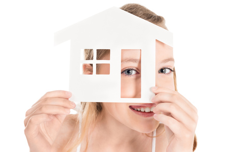 obscured view of little smiling girl holding house model isolated on white