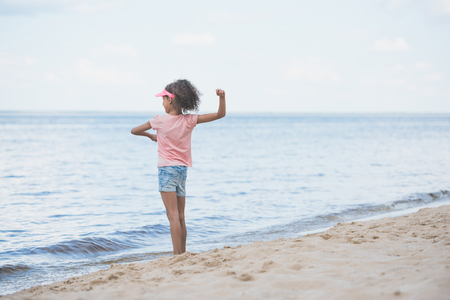 side view of little african american girl throwing stones at seaside Standard-Bild - 102507136