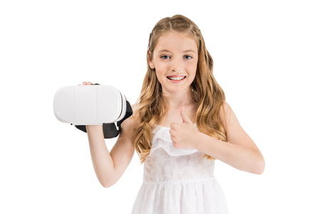 portrait of smiling little girl with virtual reality headset showing thumb up isolated on white