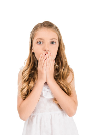 portrait of emotional little caucasian girl looking covering mouth with hands isolated on white