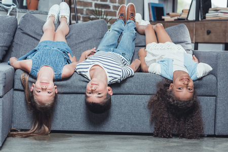 multiethnic smiling children looking at camera while lying on sofa at home