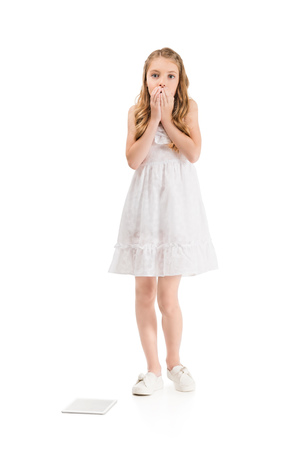 emotional little girl covering mouth with hands with tablet isolated on white Foto de archivo