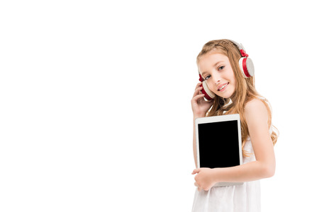 portrait of smiling little girl in headphones holding tablet in hands isolated on white
