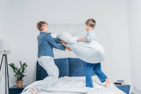 little boys in pajamas jumping on bed and having pillow fight at home 스톡 콘텐츠 - 103198562