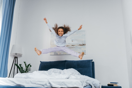happy little african american girl in pajamas jumping on bed 스톡 콘텐츠