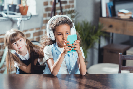 little girl looking how african american friend in headphones using smartphone while siting at table Stock Photo