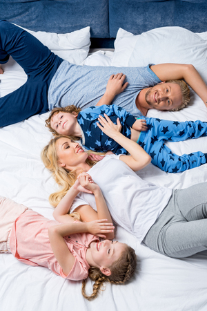 top view of happy young family lying together in bed