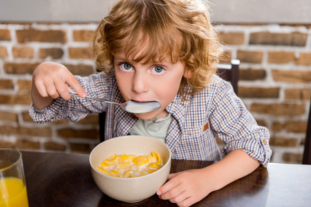 adorable little boy eating corn flakes and looking at camera Stockfoto