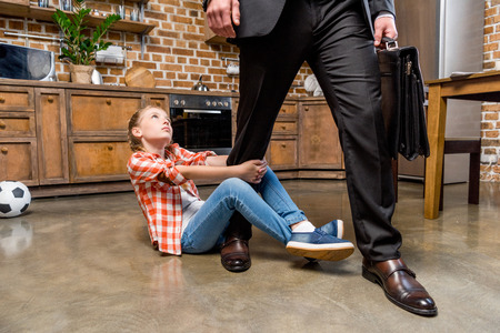 cropped shot of upset little girl hugging leg of busy father not letting him go Stockfoto