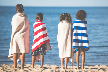 rear view of kids in colorful towels standing together on beach