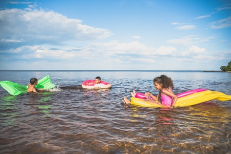 multiethnic little children swimming on colorful inflatable mattresses at sea together Stok Fotoğraf