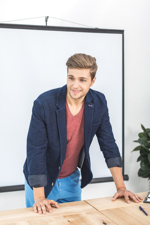 portrait of young smiling businessman leaning on table in office