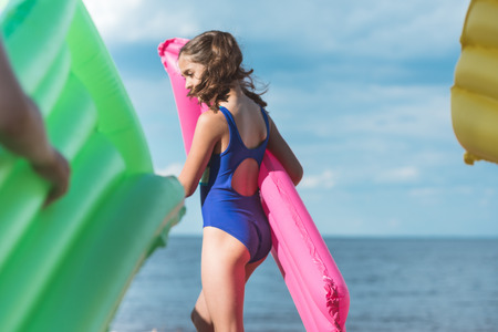 side view of little girl holding inflatable mattress while walking on beach