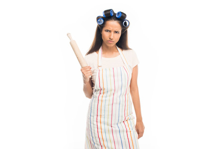 Angry housewife with curlers standing with rolling pin in hand , isolated on white