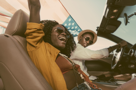 side view of smiling african american couple with american flag riding car Stock Photo