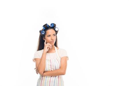 Young thoughtful housewife with curlers, wearing apron, isolated on white