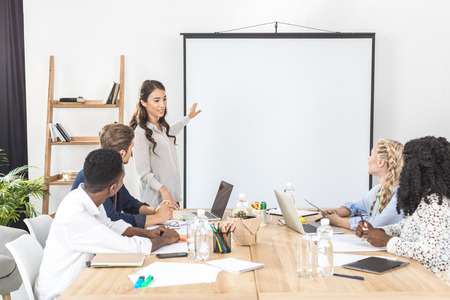 young asian businesswoman pointing at projection screen while making presentation in office Imagens