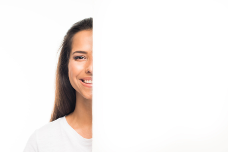 Happy woman standing behind and looking out of large blank white banner with copy space, isolated on white