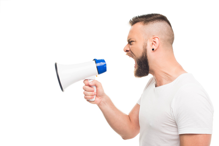 Portrait og young aggressive man using megaphone, isolated on white