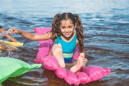 cheerful little girl swimming on inflatable mattresses at sea Banque d'images - 102892153